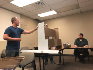men demonstrating manufacturing project to co workers using cardboard cutout